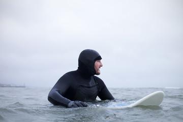 Surfer Wearing Wetsuit Floating With Board In Wintery Sea