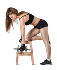 Cutout portrait of muscular young woman lifting a dumbbell for training back muscles