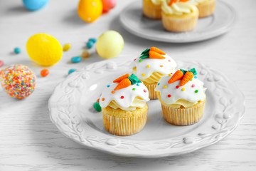 Plate with Easter cupcakes and eggs on wooden table