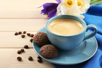 Cup of coffee with cookies and flowers on wooden table