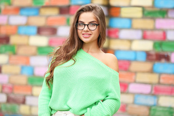 Attractive young woman on blurred brick wall background