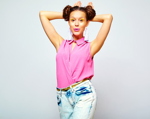 portrait of cheerful fashion hipster girl in casual colorful vivid hipster blue and pink summer clothes jeans on gray background making rabbit ears