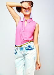 portrait of cheerful fashion hipster girl in casual colorful vivid hipster blue and pink summer clothes jeans on gray background