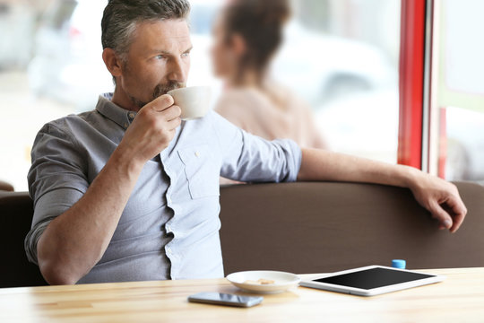 Businessman resting with cup of coffee in cafe