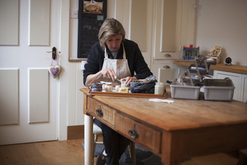 Mature Woman Sitting At Table Making Ceramic Pot