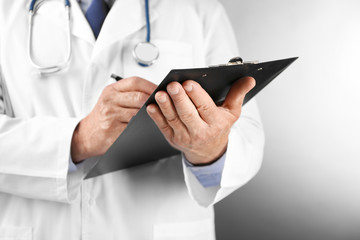 Professional doctor with clipboard on grey background