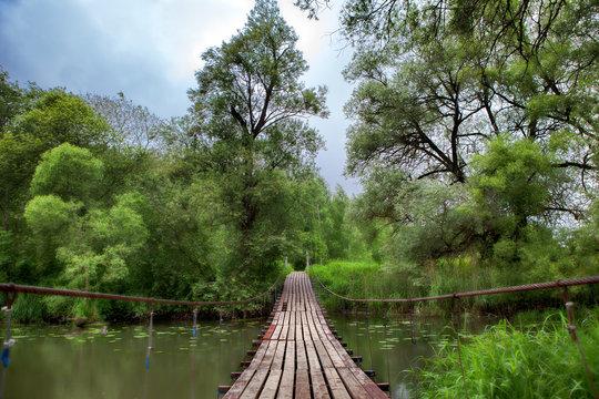 Wooden old swinging bridge over river beautiful Landscape