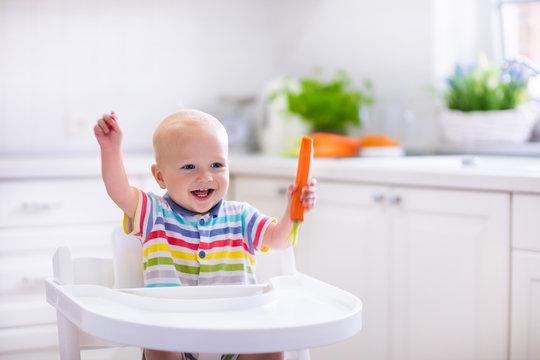 Little baby eating carrot