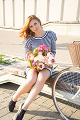 Young beautiful woman in striped dress with bicycle