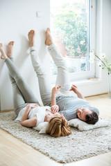 Deurstickers Ontspanning Junges Paar liegt im Wohnzimmer auf einem Teppich
