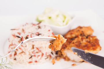Pork chop (covered in breadcrumbs), three color rice and cucumber salad being eaten with a fork and a knife
