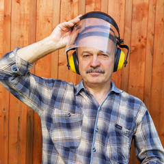 elderly man in a protective building headphones and mask