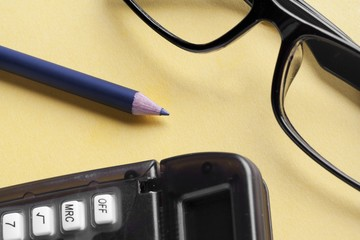 cropped image of spectacles color pencil and calculator