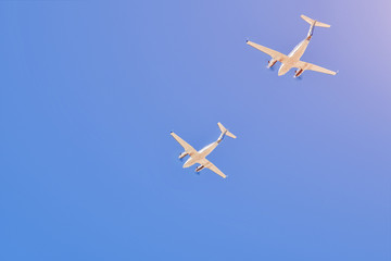 Two small aircrafts flying in a blue sky