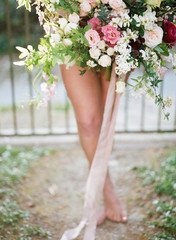 Woman with bare legs holding bouquet of flowers