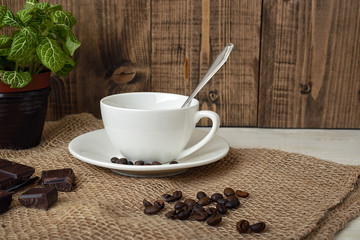 Close-up of white cup and coffee beans with chocolate on the table