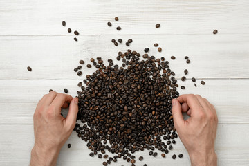 Close-up hands of man on a wooden surface with spreaded coffee beans