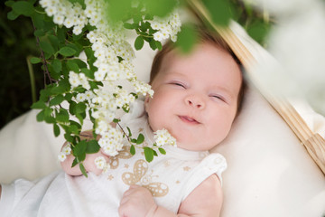 Horizontal picture of the smiling newborn baby outside in the blossoming garden