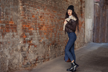 Outdoor lifestyle portrait of pretty young girl, wearing hipster swag grunge style on urban background. Wearing hat and jeans with backpack. Spring fashion woman. Toned style instagram filters.