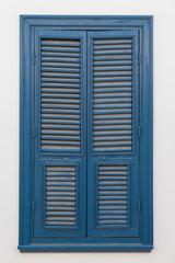 Closed blue window on light wall