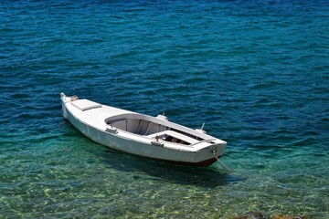 Tiny wooden boat on an azure sea