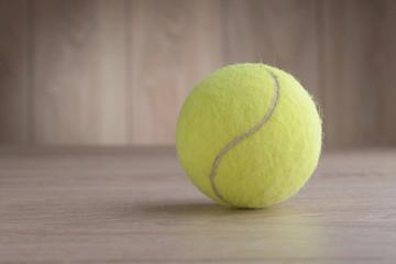 Tennis ball on a wooden floor.