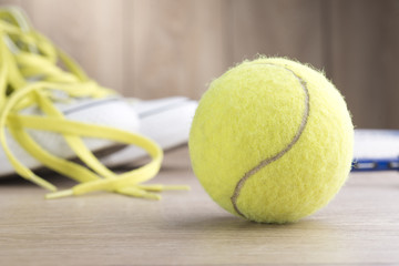 Rackets, tennis ball,  shoes on a wooden floor.