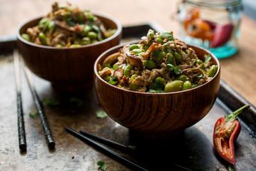 Tofu stir fry in bowls with chopsticks