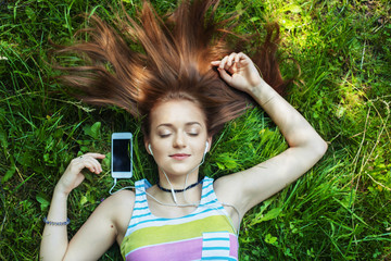 woman lying in park and listening to music