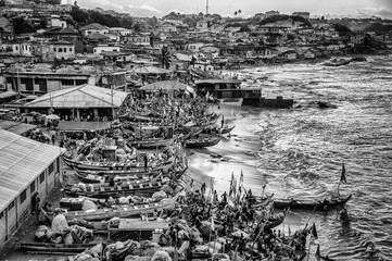 Fishing boats on coast by village, cape coast, ghana, black and white image