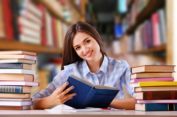 Young woman with books in library