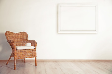 Cozy chair and picture frame on wall background