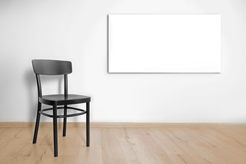 Black chair and picture frame on wall background