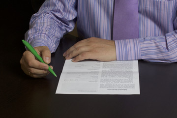 A man reads a model release before signing it. On the table lies a dark pure form. The hand holds a pen to fill out and sign.