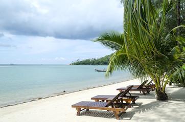 Sunbeds beside the tropical beach and ocean. Thailand.