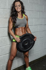 Female fitness model holding barbell weight.