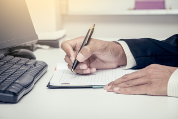 Businessman writing on notebook with pen in the office