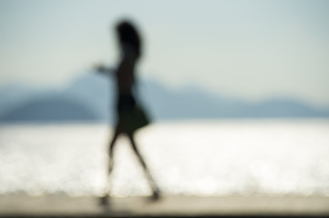 Abstract defocused silhouette of Brazilian woman walking in front of a scenic sea background in Rio de Janeiro, Brazil