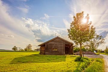 Old barn near farm at sunset
