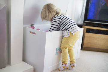 Young Girl Reaching Into Wooden Toy Box