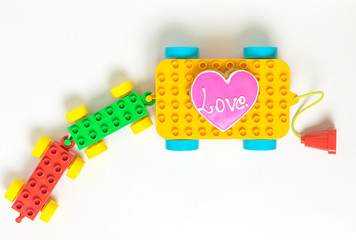 Colorful Toy Block Cart carrying a Heart Love cookie on white backgroud