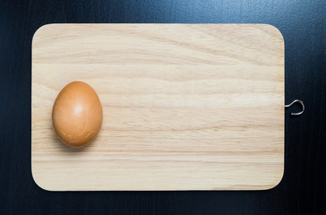 Cracked egg on wooden tray. Broken egg in kitchen.