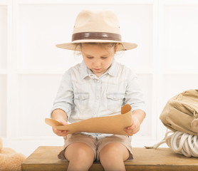 87739ab1e896d Adorable little girl in a safari hat and explorer clothes hiding her ...
