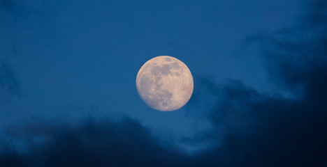 Full glowing moon closeup on  blue sky and dark misty clouds