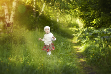 little girl walks in the morning sun in the summer in the Park