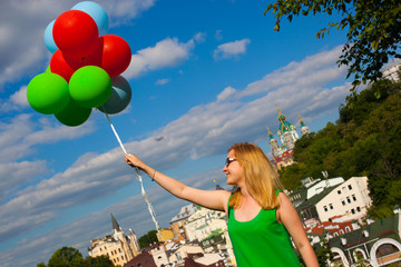 Happy young woman in green dress holding colorful balloons and flying over a panorama of old Kiev, Ukraine