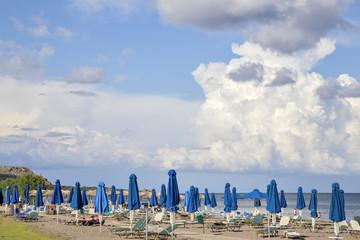Пустынный пляж с лежаками и зонтиками в межсезонье.