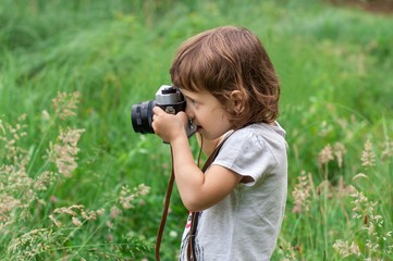 Little girl is photographing flowers in green grass