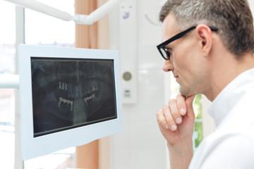 Male dentist looking teeth on digital X-Ray computer monitor