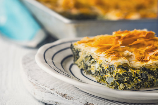 Greek pie spanakopita in the ceramic plate on the white  table  horizontal